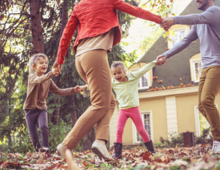 Family playing in the fall leaves